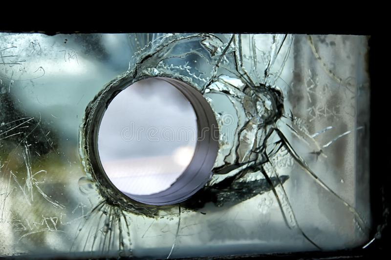 Circular hole through shattered glass. A picture of a circular hole through shattered glass in Alcatraz prison stock photography