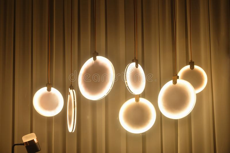 Circular Led chandelier lighting in the shop window. Circular led chandeliers in the shop window at night stock image