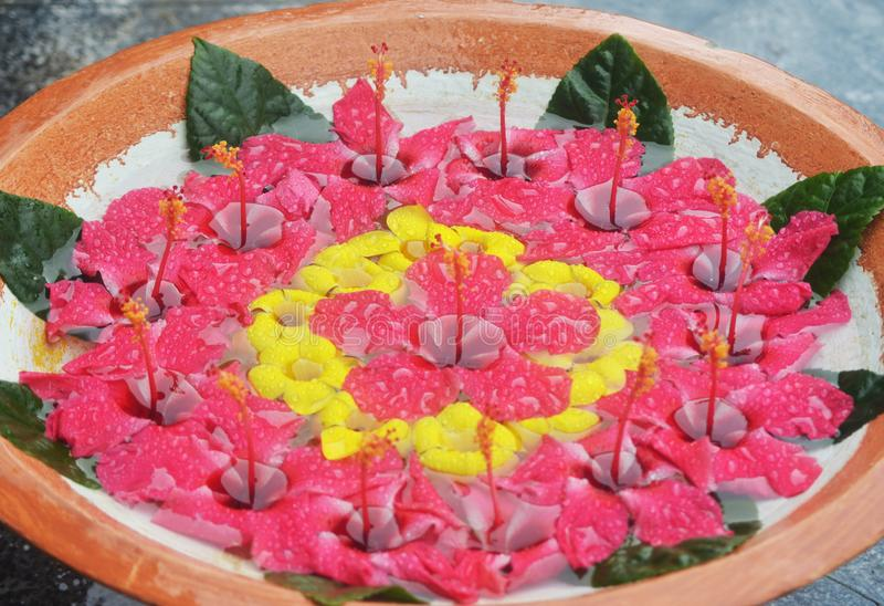 A circular pattern of red and yellow flowers floating in a terracotta bowl. stock image
