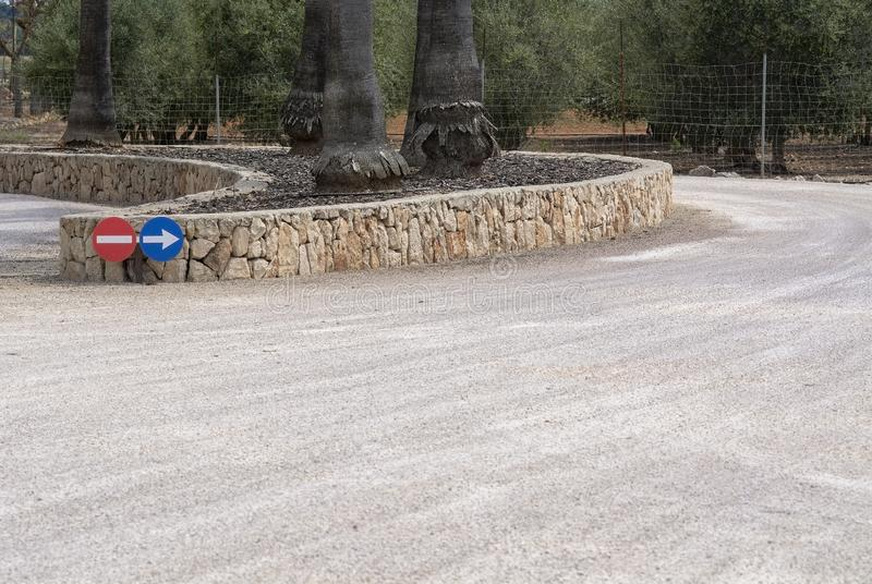 Circular road signs direction stone wall. Circular road signs for direction and stone wall shape with trees in Mallorca, Spain royalty free stock photo