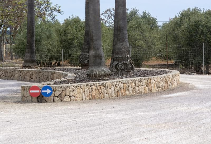 Circular road signs direction stone wall. Circular road signs for direction and stone wall shape with trees in Mallorca, Spain royalty free stock photography