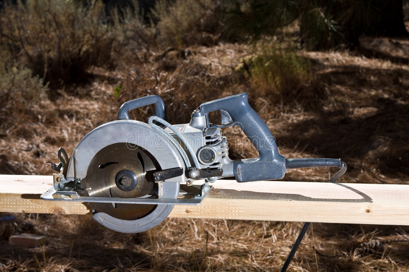Circular saw. On board with forest in background stock photo