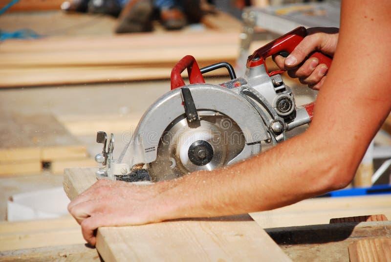 Circular saw. Man using circular saw at construction site royalty free stock image