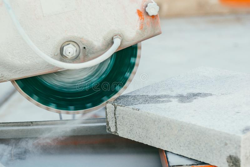 Circular saw cuts a large piece of granite tiles for pavement.  stock photos