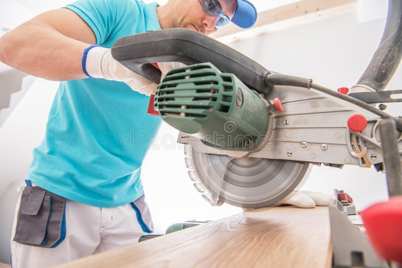 Circular Saw Cutting Job. Contractor Worker and the Power Tool. Remodeling Theme stock photos