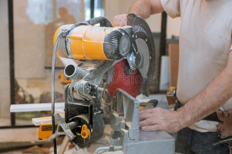 Circular saw cutting new baseboard for renovation home. Circular saw cutting new baseboard for new home construction interior finish details, sawing, moldings royalty free stock photos