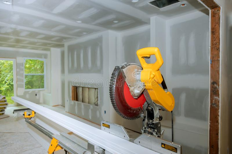 Details new home installing construction building industry interior circular saw cutting wooden base molding. Circular saw cutting wooden base molding new home stock photography