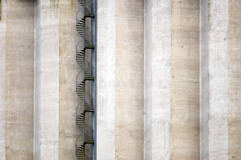 Circular stair. A circular metal stairway winding up in front of a huge concrete frontage royalty free stock images