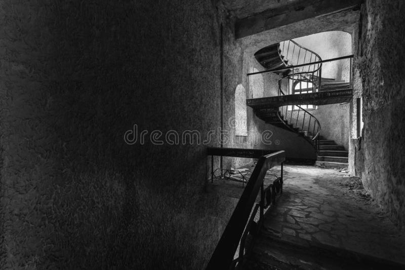 The circular staircase with steps in an abandoned house with cop. Y-space, black and white image. The concept of the modern loft royalty free stock photo