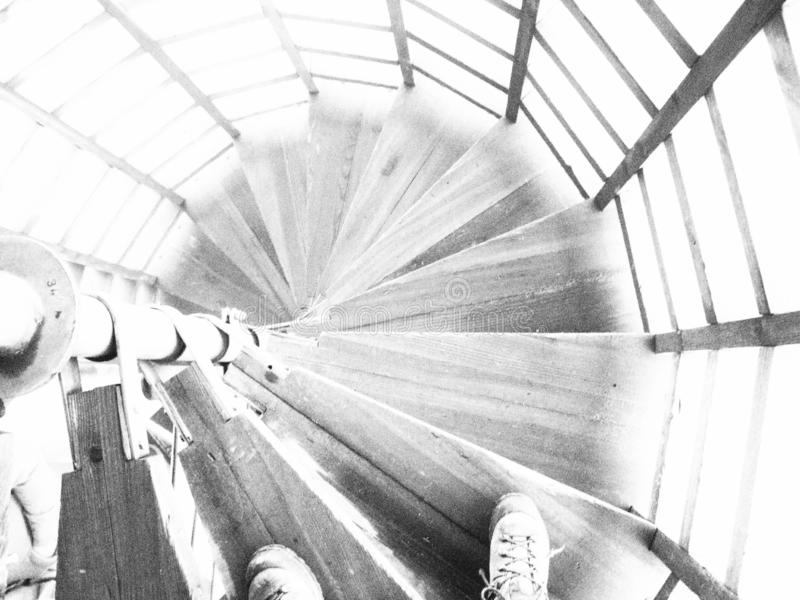 Circular stairs in tower at the top of the Giant mountains, Czech republic with shoes at the begining. Black and white. Photo, grey too stock photo