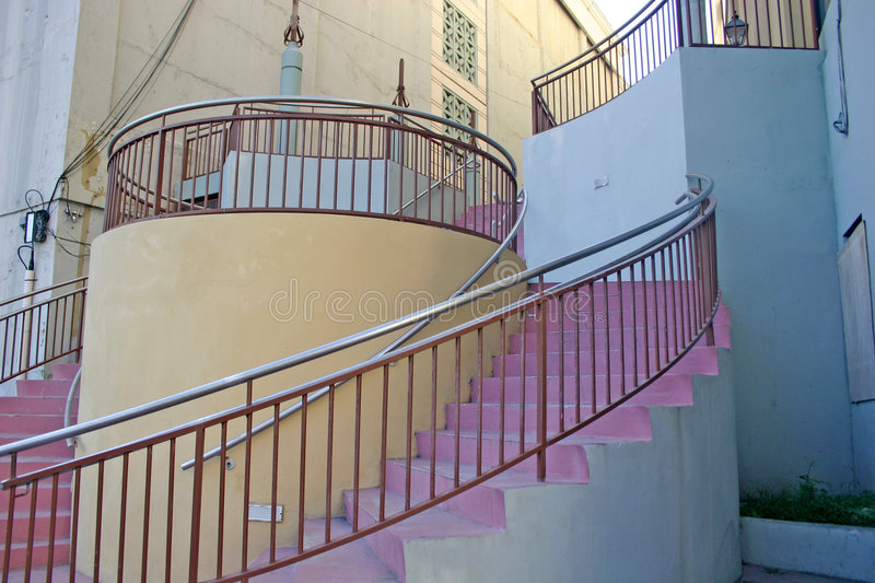 Circular stairway. Unusual modernistic, circular stairway with pink stairs, white and blue walls and silver railings royalty free stock photo