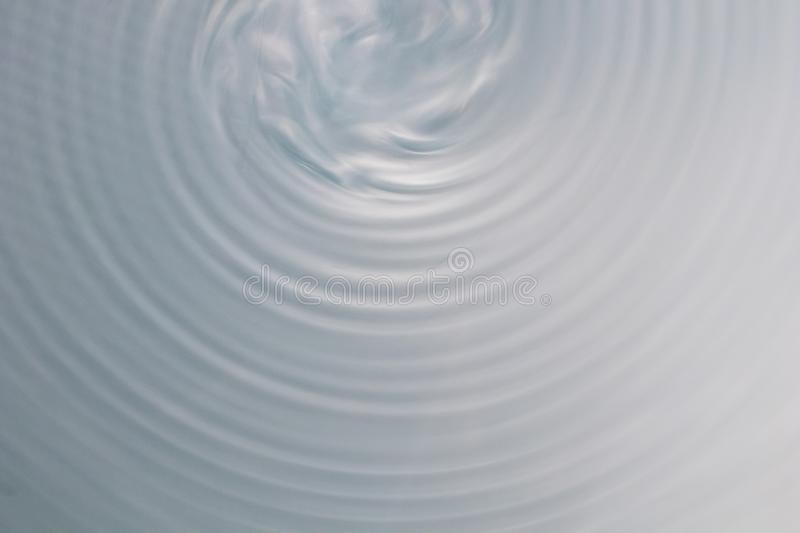 Circular wave motion in a fluid system. blue gray background for. A liquid pushed into a circular motion. waves and concentric circles with ripples as abstract royalty free stock image