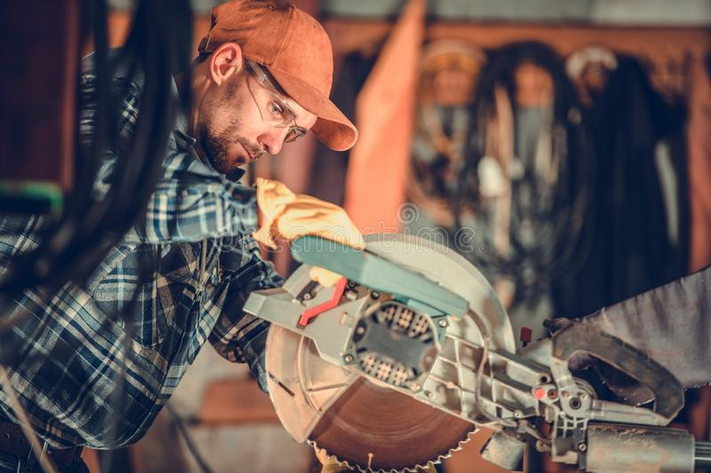 Circular Wood Saw Job. Caucasian Contractor Worker and the Cutting Equipment royalty free stock images
