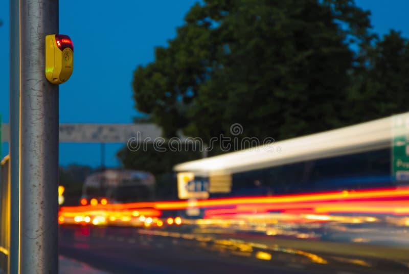 Circulation urbaine à la soirée, fin de passage piéton de bouton d'attente vers le haut des lumières jaunes et de voitures image stock