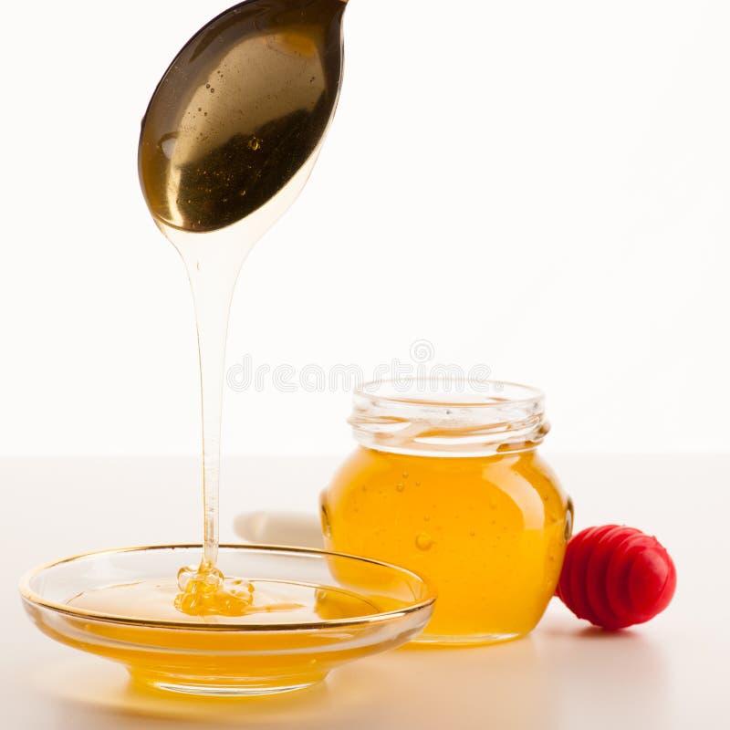 Circuler liquide d'or collant doux sur le plat transparent à côté de g image stock