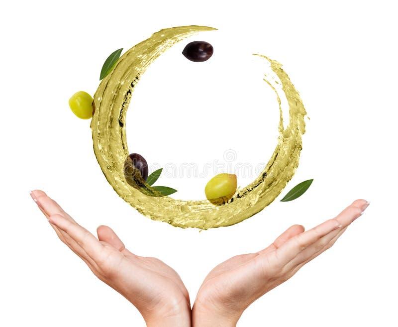 Circulez l'?claboussure d'huile d'olive avec des olives dans des mains femelles photos libres de droits