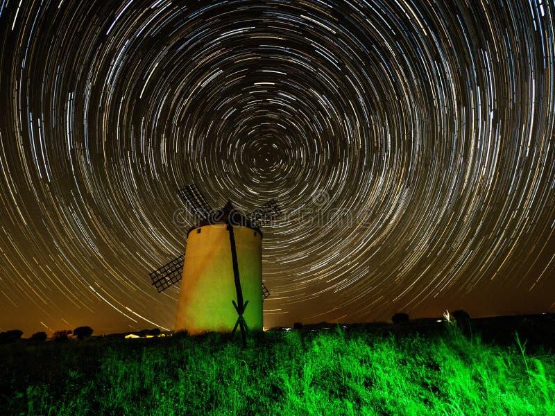 Circumpolair over een windmolen bij nacht stock afbeelding