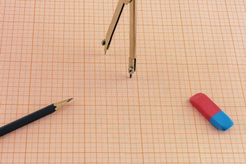 Circunde o eliminador e um lápis em uma folha do papel de gráfico imagens de stock