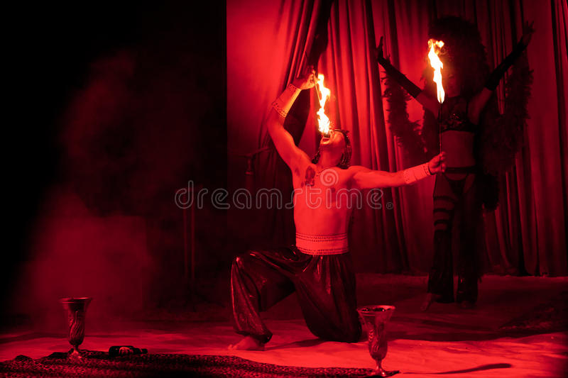 Circus artist swallowing flames. Exciting entertainment by Orlando Circus, Romania, with live fire eating performance with flaming torches, red light background royalty free stock photo
