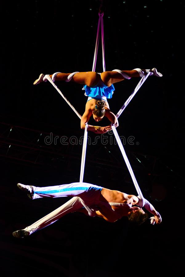 Circus Artists, Teamwork, Acrobats Couple, Aerial Gymnast Performance. Couple of acrobats performing on aerial white ropes. Circus party sponsored by Figo