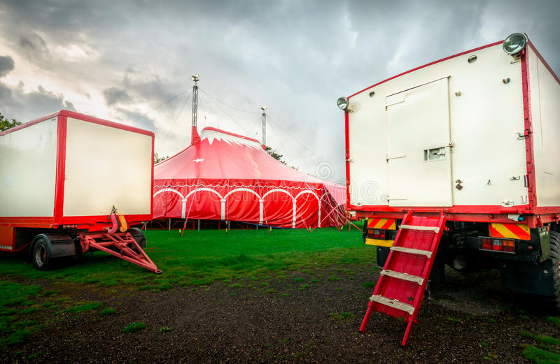 Circus has come to town!. Two trailers in a field, one with a stair, and a red circus tent in the middle, all in red and white royalty free stock photo