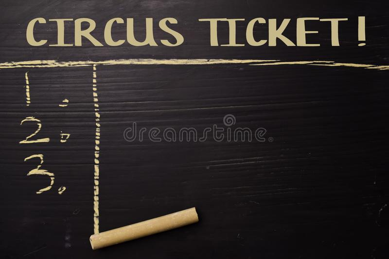 Circus Ticket! written with color chalk. Supported by an additional services. Blackboard concept royalty free stock photos