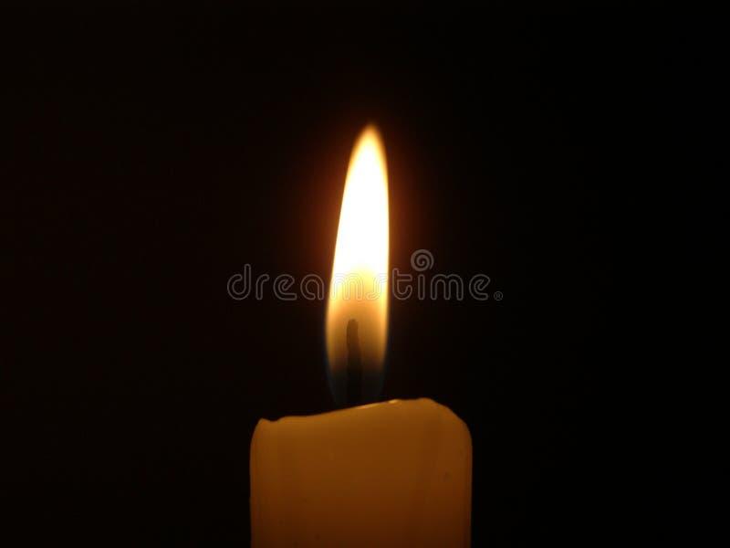 cirez la bougie brûlante dans une chambre noire avec le foyer plamy jaune sur la flamme images libres de droits