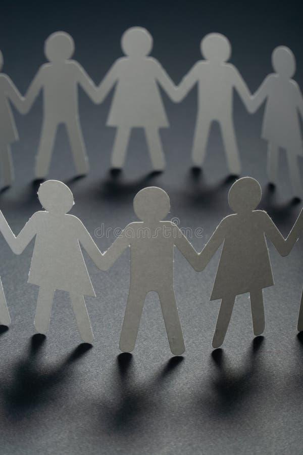 Cirkel av pappers- folk som rymmer händer på mörk yttersida Gemenskap fackligt begrepp Samhälle och service royaltyfria foton