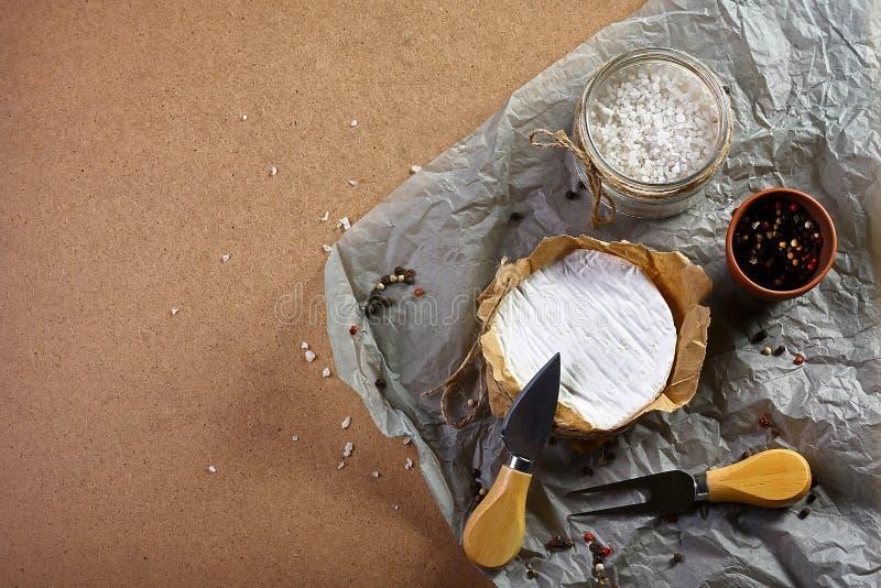 Cirkel för sammansättningscamembert- eller brieost, krydda på gammalt kraft papper, ostportionkniv bild för bästa sikt med kopier royaltyfri fotografi