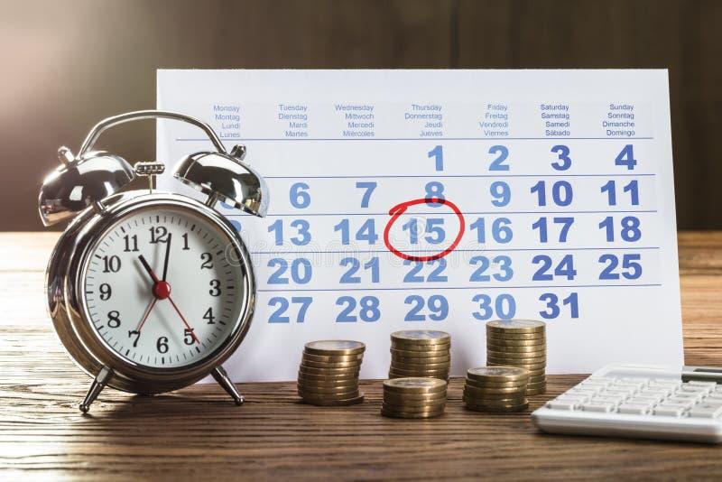 Cirkel som markeras på kalender med klockan och mynt på skrivbordet arkivfoton