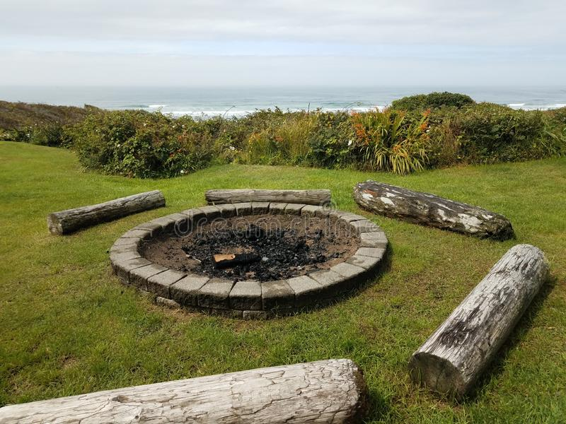 cirkelbrandkuil met houtskool en logboeken bij strand stock foto's