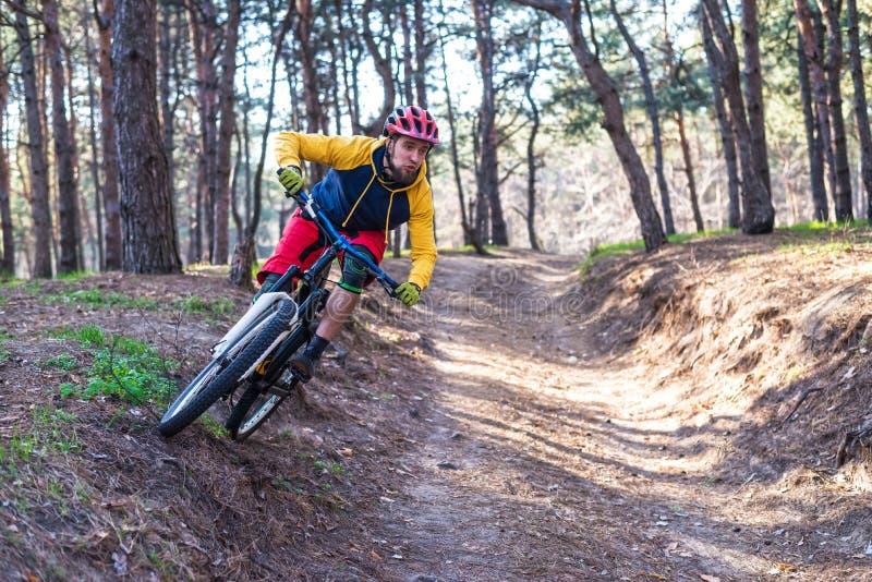 Cirkelend, een fietser in heldere kleren die een bergfiets berijden op de rand van de helling Actieve levensstijl stock foto's