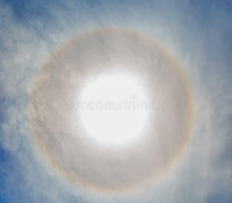 Cirkelshalo in de blauwe bewolkte hemel rond van de zon royalty-vrije stock afbeeldingen