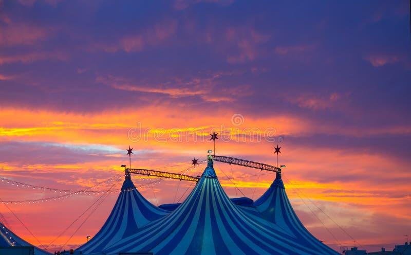 Cirkustält i dramatisk en färgrik solnedgånghimmel arkivfoto
