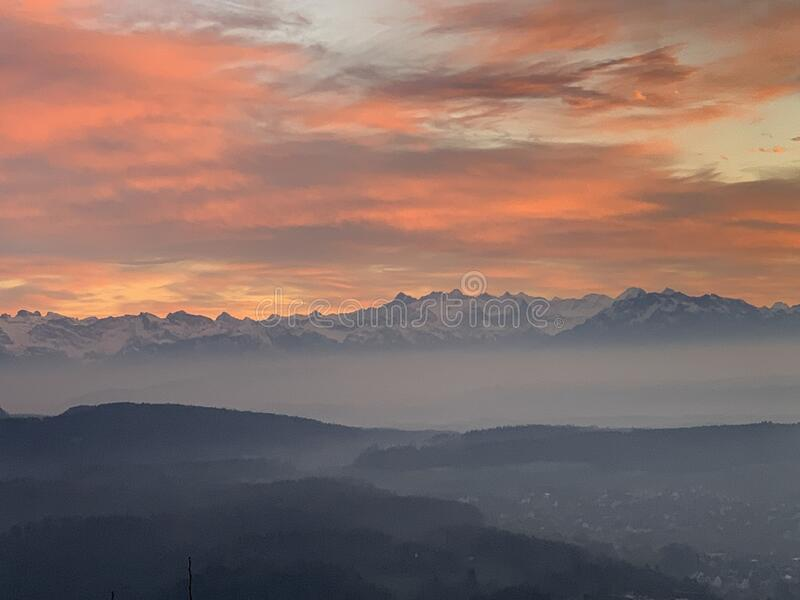 Cirrus clouds of orange and pink above Alps panorama with fog covering partially hills as seen from Uetliberg Zurich Switzerland. Among small hills in the royalty free stock photography