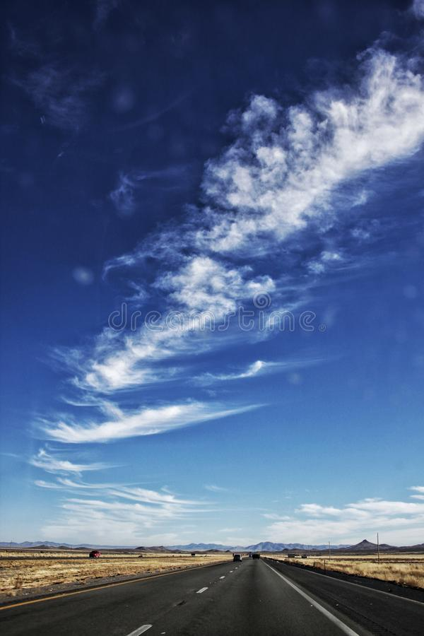 Cirrus Clouds over Empty Black Road royalty free stock photo