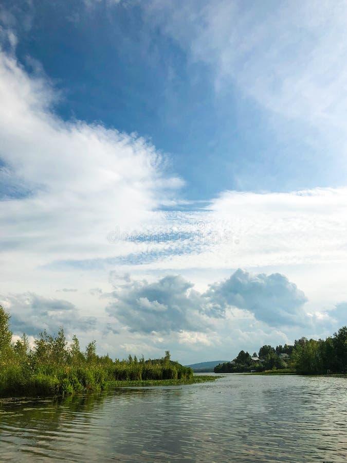 Cirrus e Cumulus nuvole in cielo Vista del lago e delle isole con alberi e vegetazione Una brezza luminosa sta soffiando soffiatu fotografie stock libere da diritti