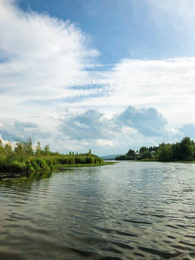 Cirrus e Cumulus nuvole in cielo Vista del lago e delle isole con alberi e vegetazione Una brezza luminosa sta soffiando soffiatu fotografie stock