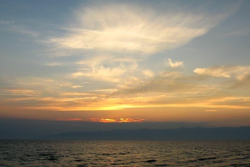 Cirrusmolnmoln i aftonhimlen över vatten, konturn av bergen på horisonten, solen går ner inget royaltyfri foto
