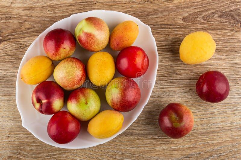 Ciruelos, albaricoques, nectarinas en plato, frutas en la tabla Visi?n superior fotos de archivo libres de regalías