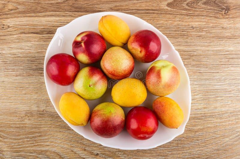 Ciruelos, albaricoques, nectarinas en plato en la tabla de madera Visi?n superior imagenes de archivo