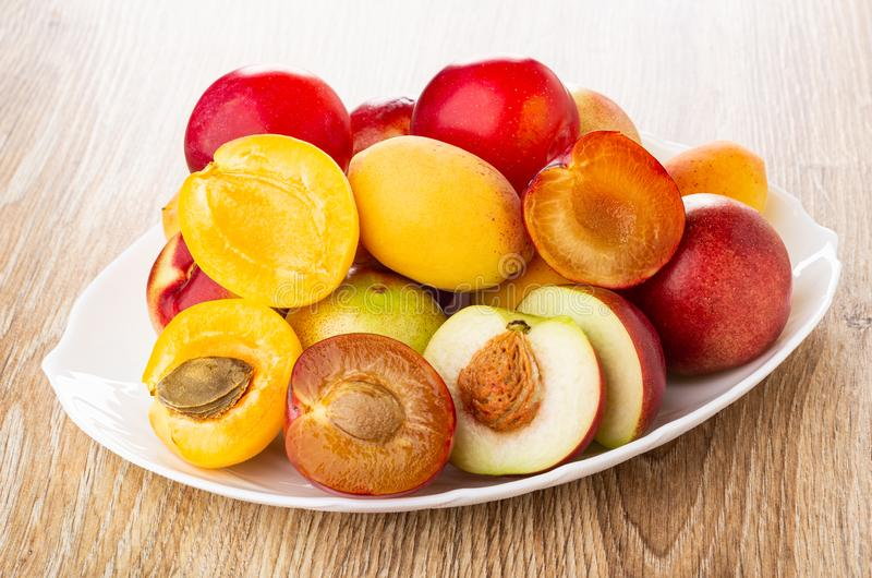 Ciruelos, albaricoques, nectarinas, mitades de frutas en plato en la tabla fotos de archivo libres de regalías