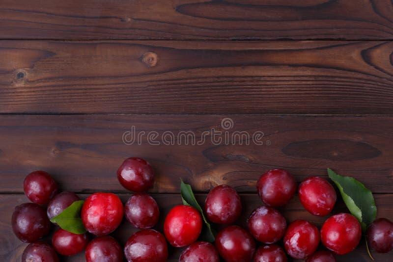 Ciruelos dulces jugosos frescos en la tabla de madera, espacio de la copia para los advertis fotografía de archivo