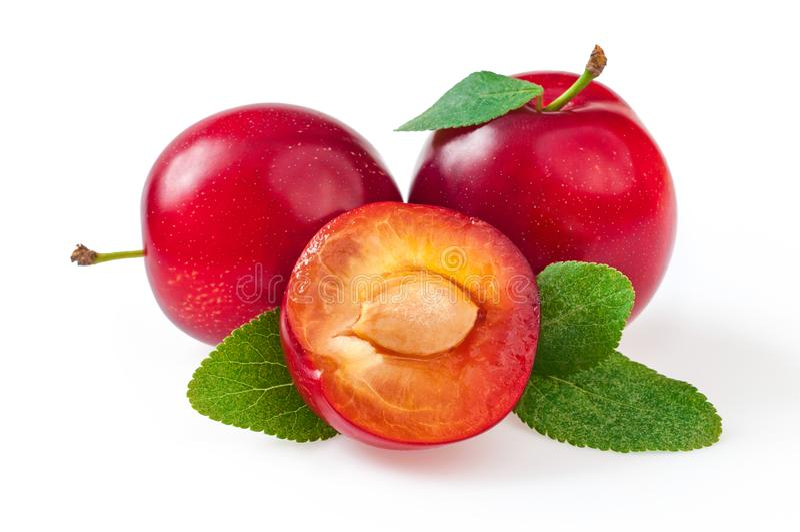 Ciruelos rojos deliciosos dulces con las hojas, y medio ciruelo del corte Cierre imágenes de archivo libres de regalías