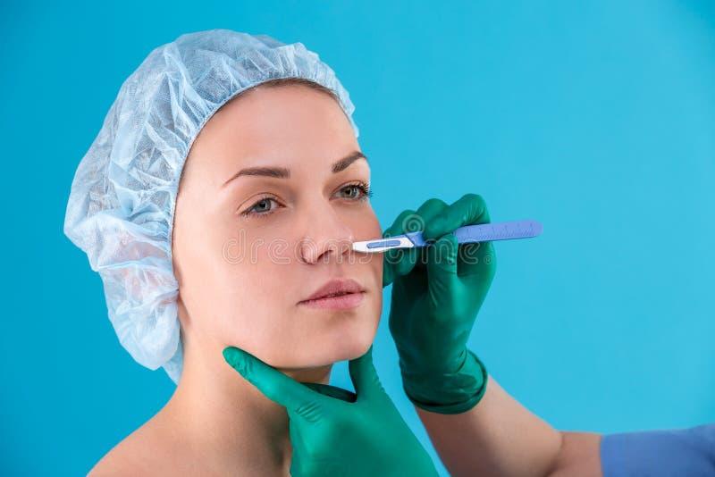 Cirujano cosmético Examining Female Client en oficina Doctor que comprueba la cara de la mujer, el párpado antes de la cirugía pl fotografía de archivo
