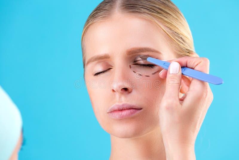 Cirujano cosmético Examining Female Client en oficina El doctor dibuja líneas con un marcador, el párpado antes de la cirugía plá fotos de archivo libres de regalías