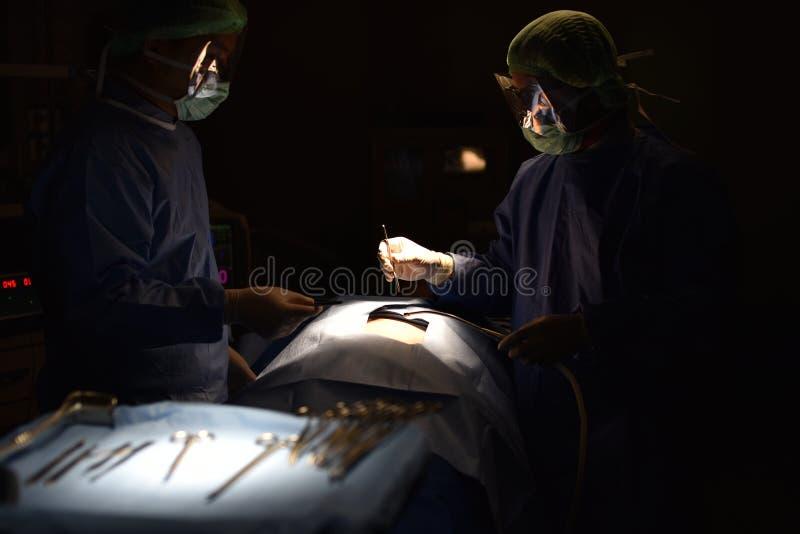 Cirujano de las personas en el trabajo en sala de operaciones Luz quirúrgica en la sala de operaciones imagen de archivo