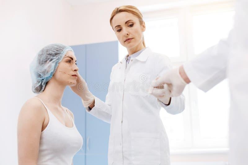 Cirujano de sexo femenino serio que realiza una operación imagen de archivo libre de regalías