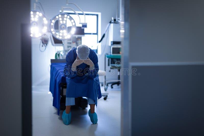 Cirujano de sexo femenino trastornado que se sienta en sitio en funcionamiento de la cama fotos de archivo