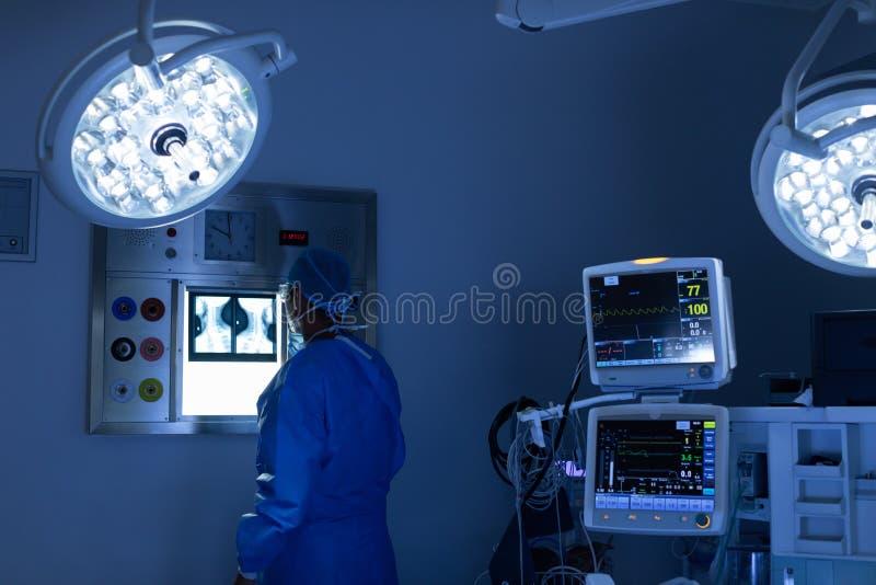 Cirujano de sexo masculino que lee el rayo de x en sala de operaciones en el hospital imagenes de archivo